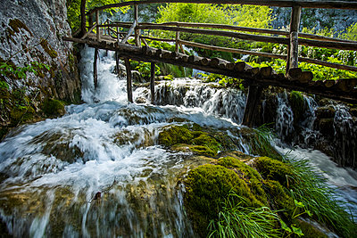 Wooden footbridge over waterfall - p555m1491638 by Steve Smith