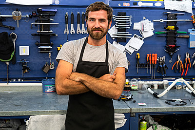 Smiling mechanic standing in workshop - p623m2214736 by Frederic Cirou