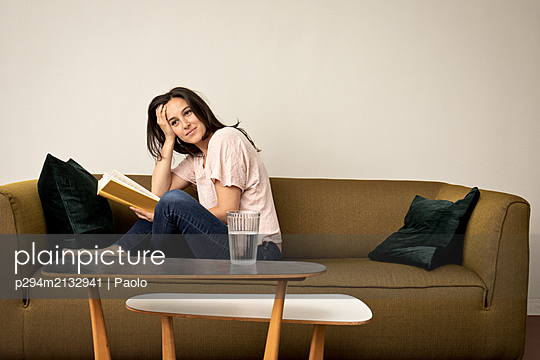 Woman sits on sofa reading book - p294m2132941 by Paolo
