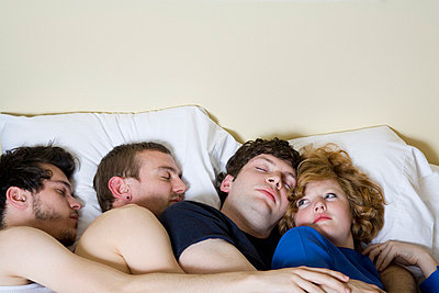 Four friends lying in a bed together - p3018998f by Antenna photography