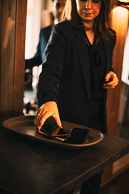 Midsection of female legal professional keeping smart phone on tray in office - p426m2127529 by Maskot