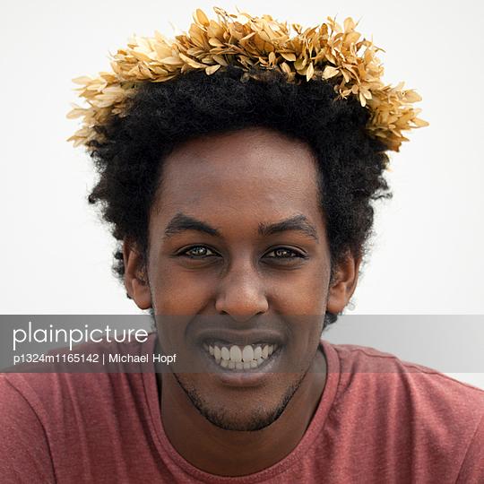 Junger dunkelhäutiger Mann mit Haarschmuck - p1324m1165142 von michaelhopf