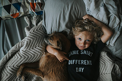 Portrait of boy with dog lying on bed - p1166m1203757 by Cavan Images