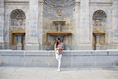 Smiling woman using her phone while leaning on a fountain in Boadilla - p1166m2136196 by Cavan Images