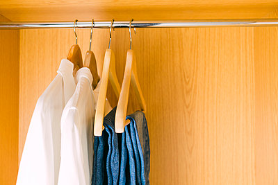 Clothes hanging in wardrobe - p1427m2109924 by Alexandra C. Ribeiro