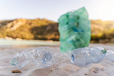 Empty plastic bottles and garbage bin full of collected plastic bottles on the beach - p300m2143691 by Daniel Ingold