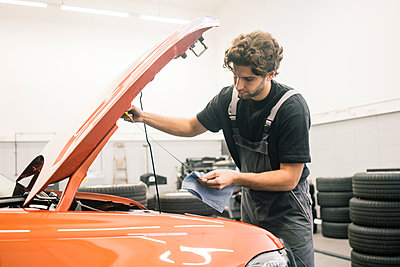 Car mechanic in a workshop working at car checking dipstick - p300m2166834 by Robijn Page
