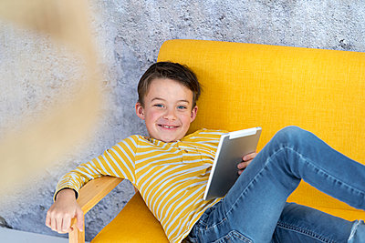 7 year old boy playing with tablet on yellow couch in front of concrete wall - p300m2170327 von Epiximages
