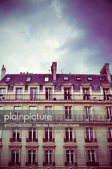 Facade of Paris apartment building with stormy sky - p1072m829291 by Neville Mountford-Hoare