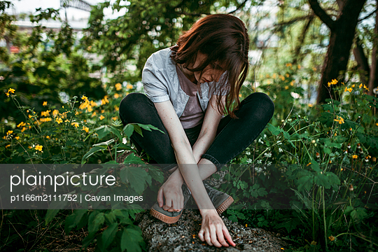 A woman is sitting on a stone in the middle of flowers - p1166m2111752 by Cavan Images