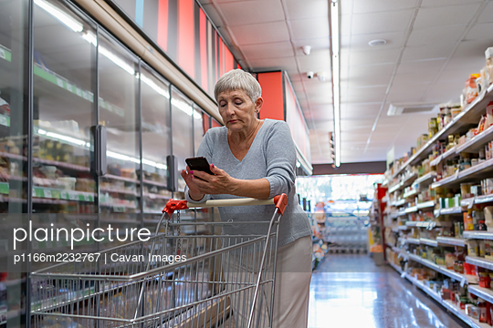 Caucasian elderly woman with white hair  shopping in supermarket - p1166m2232767 by Cavan Images