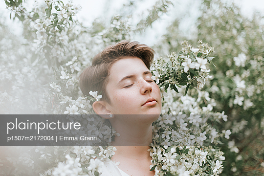 Girl with closed eyes among flowers - p1507m2172004 by Emma Grann