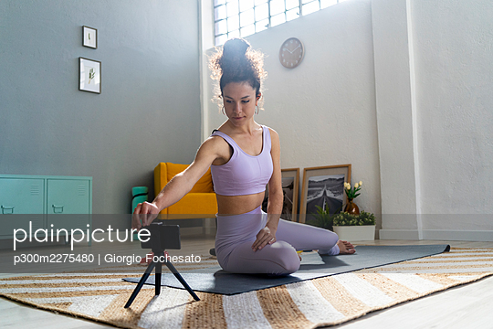 Female influencer touching smart phone while doing yoga at home - p300m2275480 by Giorgio Fochesato