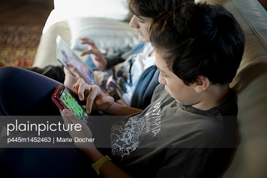 Teens playing video games - p445m1452463 by Marie Docher
