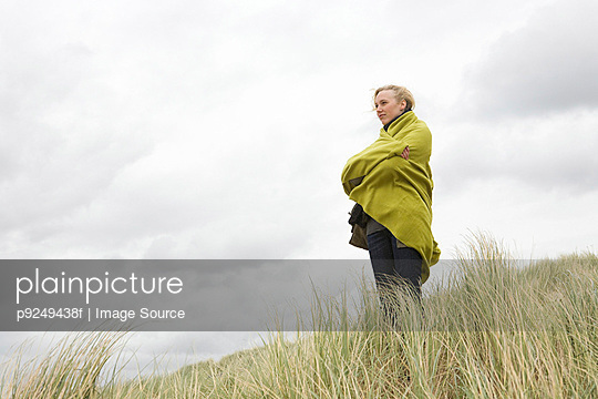Woman at the coast in blanket - p9249438f by Image Source