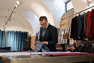 Mature tailor examining ornamental cloth - p1166m2261446 by Cavan Images