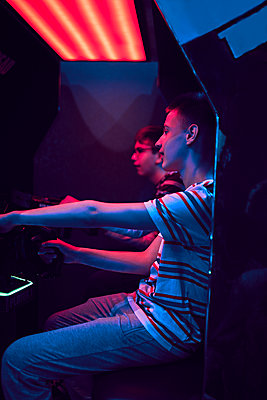 Teenage friends playing with a driving simulator in an amusement arcade - p300m2144982 by Zeljko Dangubic