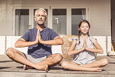 Father and daughter sitting on terrace in sunshine doing yoga - p300m2167021 by Floco Images
