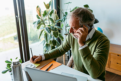 Mature man talking on mobile phone while working at home - p300m2226571 by Valentina Barreto