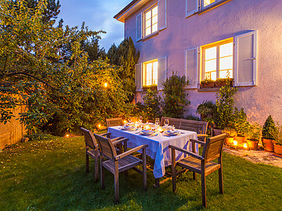 Autumnal laid table in garden in the evening - p300m981578f by Werner Dieterich