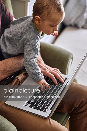 Father and baby boy using laptop together, Stay at home due to Covid-19 - p1146m2182013 by Stephanie Uhlenbrock