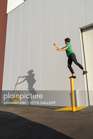 Acrobat standing on pole, casting shadow at cleaning bucket - p300m2012381 von VITTA GALLERY