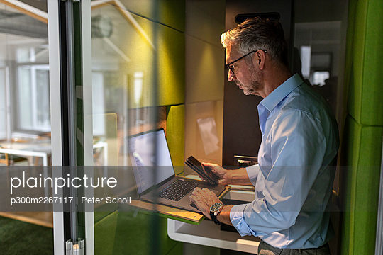 Mature businessman holding mobile phone while using laptop in soundproof cabin at office - p300m2267117 by Peter Scholl