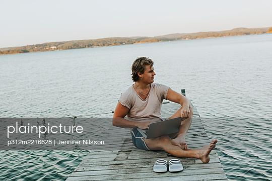 Man sitting on jetty and using laptop - p312m2216628 by Jennifer Nilsson
