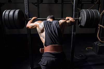 An athlete prepares to back squat at a gym. - p1166m2094523 by Cavan Images