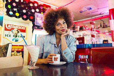 Junge Frau mit Afro in American Diner - p1301m1467395 von Delia Baum