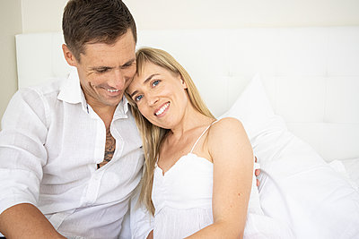 Happy couple sitting on bed, portrait - p1640m2259620 by Holly & John