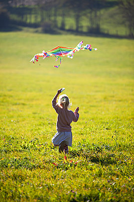 Little girl running in field with kite - p300m2103547 von Anette Christina Götz