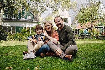Happy family sitting on grass in their garden - p300m2167325 by Kniel Synnatzschke