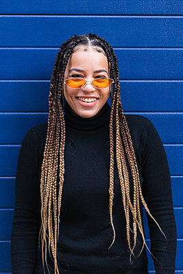 Mid adult woman with braided hair smiling while standing against blue wall - p300m2267131 by NOVELLIMAGE