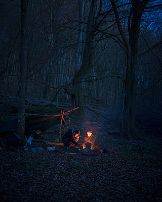 Men camping in forest at night - p352m2120233 by Gustaf Emanuelsson