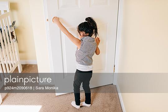 Girl opening nursery door, rear view - p924m2090618 by Sara Monika