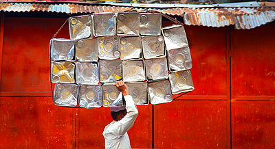 Side view of man carrying stack of metal containers on his head, walking past red metal wall. - p1100m1570953 by Mint Images