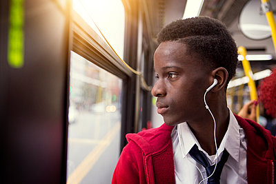 Student listening music while traveling in bus - p1166m1096595f by Cavan Images