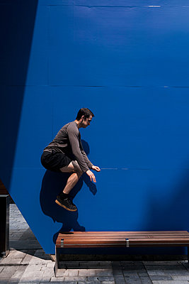 Side view of man jumping on wooden bench against blue wall during sunny day - p1166m2025389 by Cavan Images