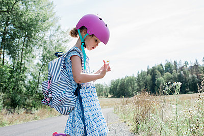 young girl with helmet on stopping to look at wild flowers in a meadow - p1166m2137933 by Cavan Images