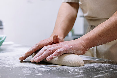Male chef kneading flour dough on kitchen counter in bakery - p300m2243650 by Jose Luis CARRASCOSA