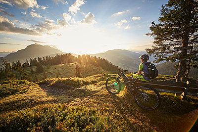 Mountainbiker takes a break and enjoys mountain views - p704m1476013 by Daniel Roos