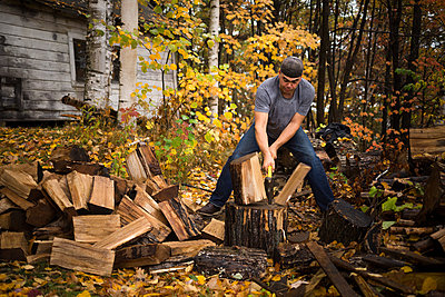 Mid adult man splitting logs in autumn forest, Upstate New York, USA - p924m1404205 by heshphoto