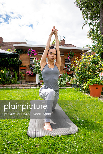 UK, London, Woman exercising on lawn in front of house - p924m2300646 by Kaori Ando