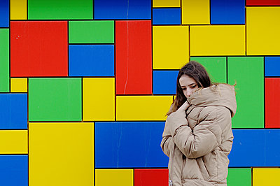 Young woman in a winter jacket against bright wall - p1412m2054338 by Svetlana Shemeleva