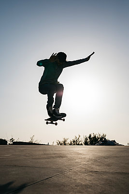 Sportive man jumping above ground with skateboard performing trick - p300m2029505 by Josep Rovirosa