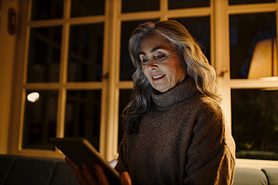 Mature woman using tablet on couch at home in the dark - p300m2156271 by Gustafsson