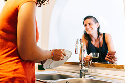 Woman washing dish while friend looking at her using smart phone - p300m2220601 by Daniel González