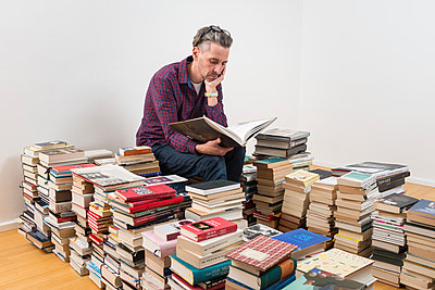 Man sitting among many books - p305m1586707 by Dirk Morla