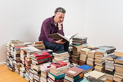 Mann sitzt zwischen vielen Büchern - p305m1586707 von Dirk Morla